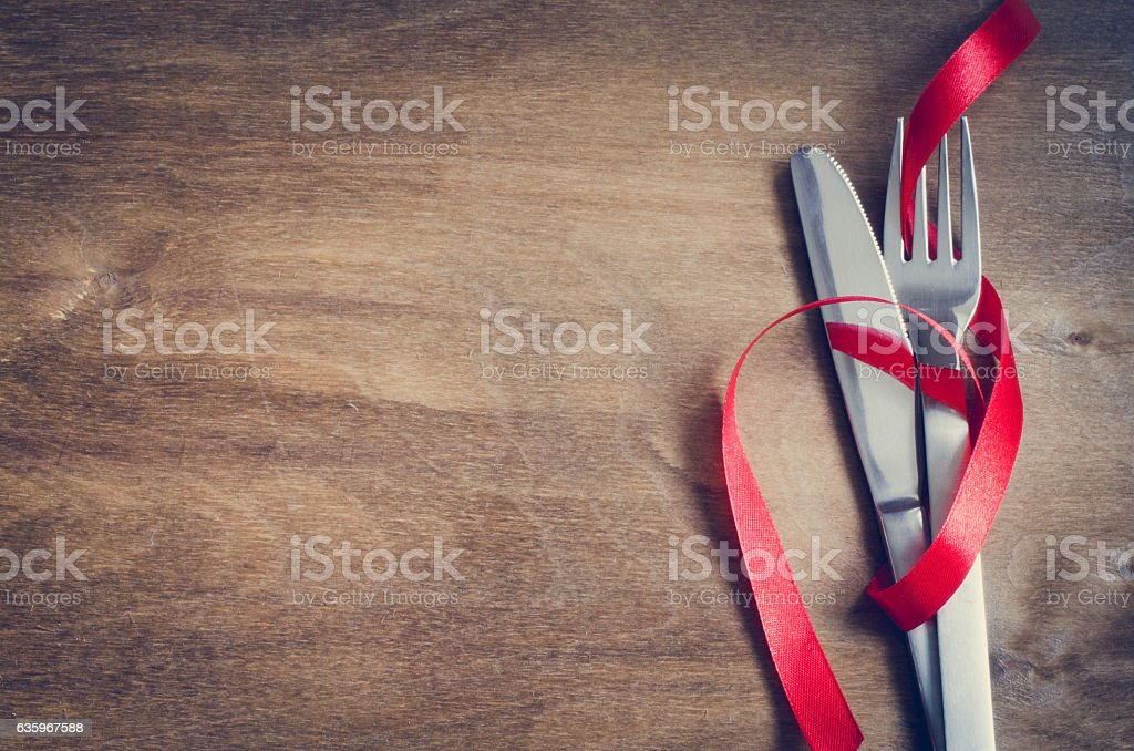 Cutlery Decorated with Red Ribbon on Wooden Background. stock photo