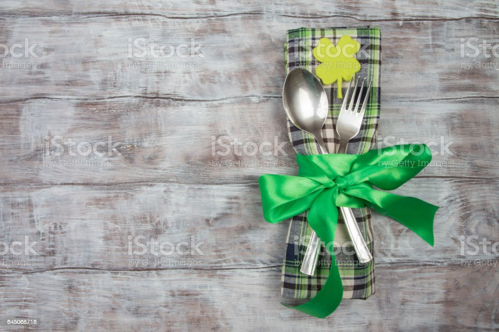 Cutlery fork, spoon, checkered napkin on table. St. Patricks Day stock photo