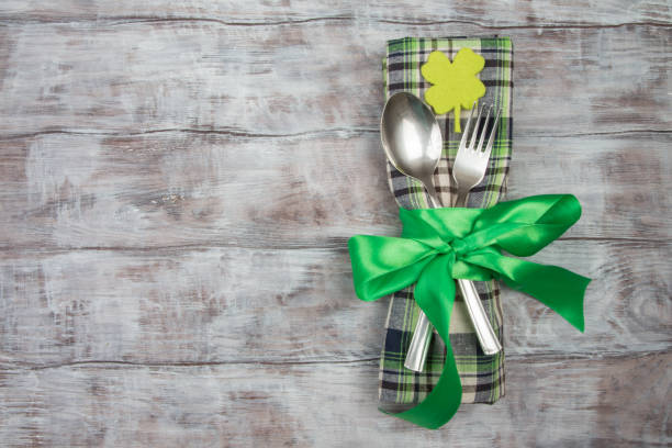 cutlery fork, spoon, checkered napkin on table. st. patricks day - st patricks day background stock photos and pictures