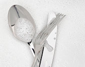 Cutlery in washing up soap bubbles - a knife, fork and spoon.