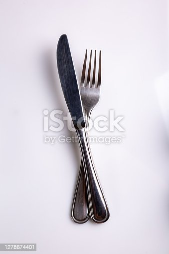Cutlery knife and fork lie crossed on a white background. View from above. Vertical orientation. High quality photo.