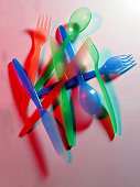 A spread of coloured plastic Spoons Knives and Forks on a white background and a red light