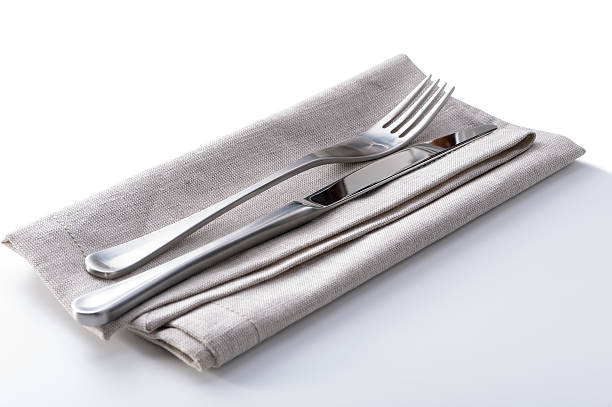 cutlery with linen napkin on white stock photo