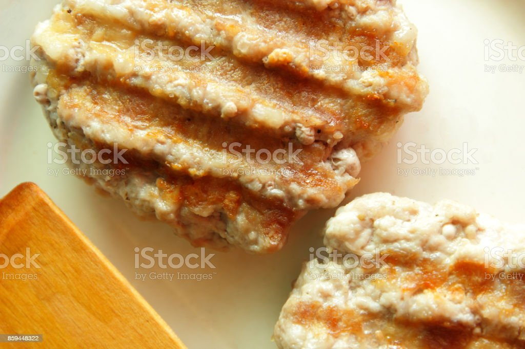 Cutlets for burger on the grill with a wooden spatula on a plate in the home kitchen stock photo