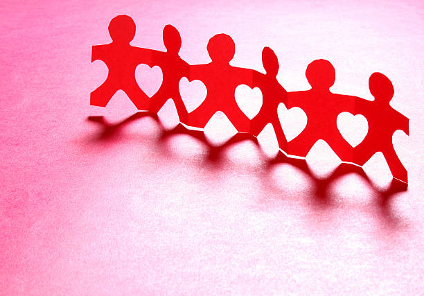 Cutout chain of lovely little men in red paper stock photo