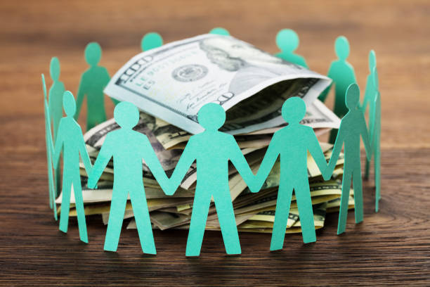 Cut-out Figures Around The Hundred Dollar Bill stock photo