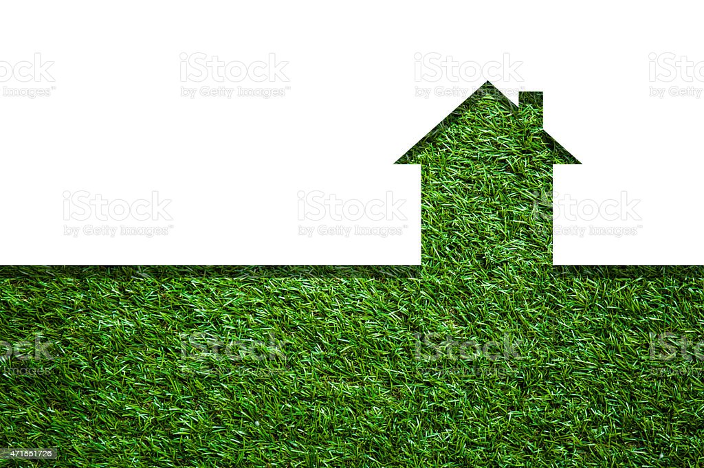 Cutout shape of a house over a green field stock photo