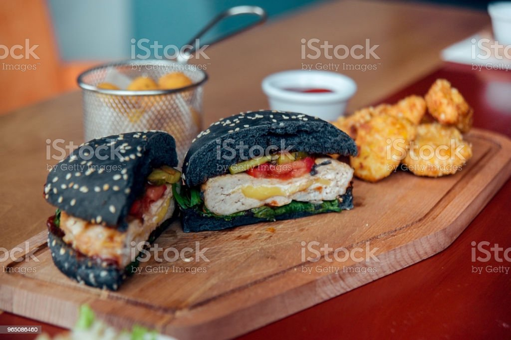 cutted black burger served with chicken nuggets and cheese balls zbiór zdjęć royalty-free