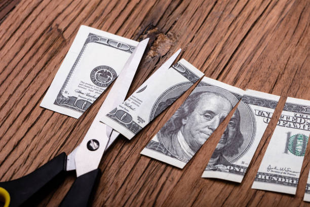 Cutted Dollar Banknote And Scissor Cutted Dollar Banknote And Scissor On Wooden Table depreciation stock pictures, royalty-free photos & images