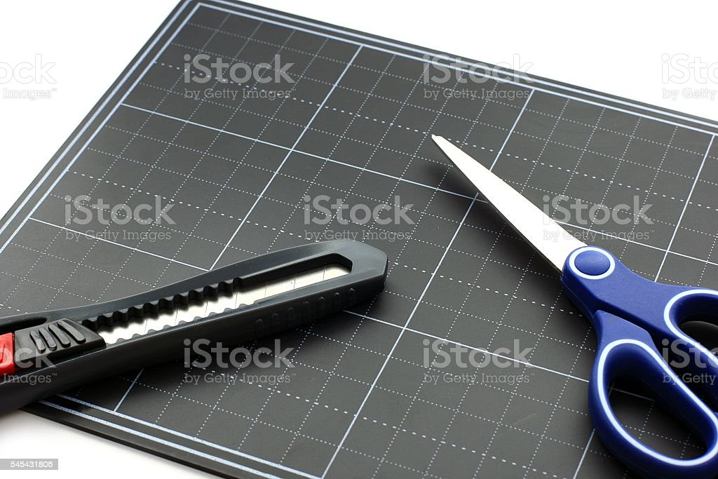 Cutter and Scissors on the Black paper cutting mat stock photo