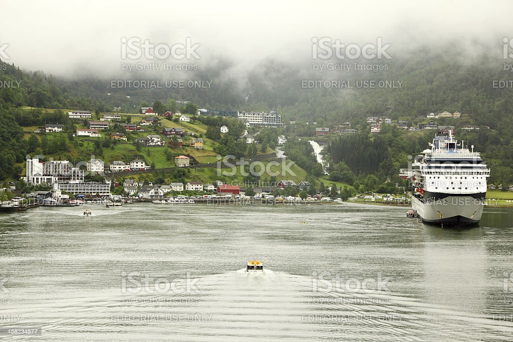 Cutter floats to shore with coastal village royalty-free stock photo