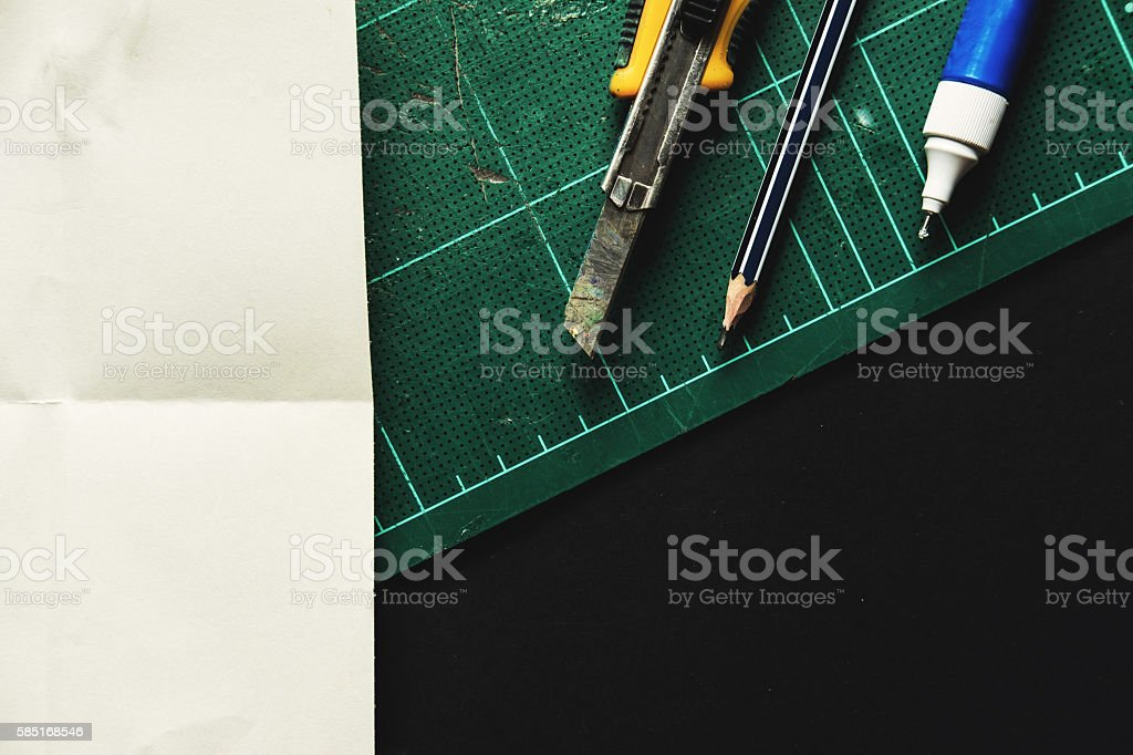 Cutter,pencil and liquid eraser and cutting mat stock photo