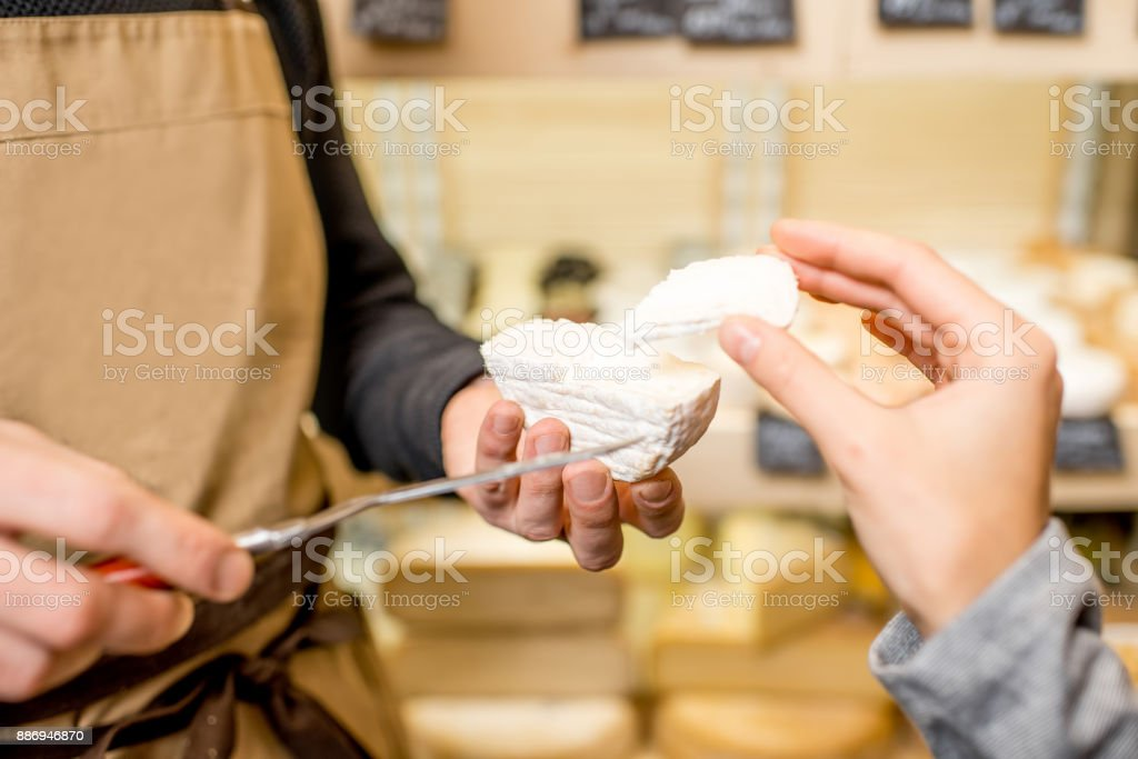 Cutting a cheese for woman customer - foto stock