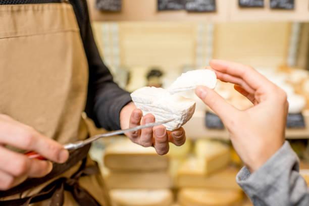 snijden van een kaas voor vrouw klant - tasting stockfoto's en -beelden