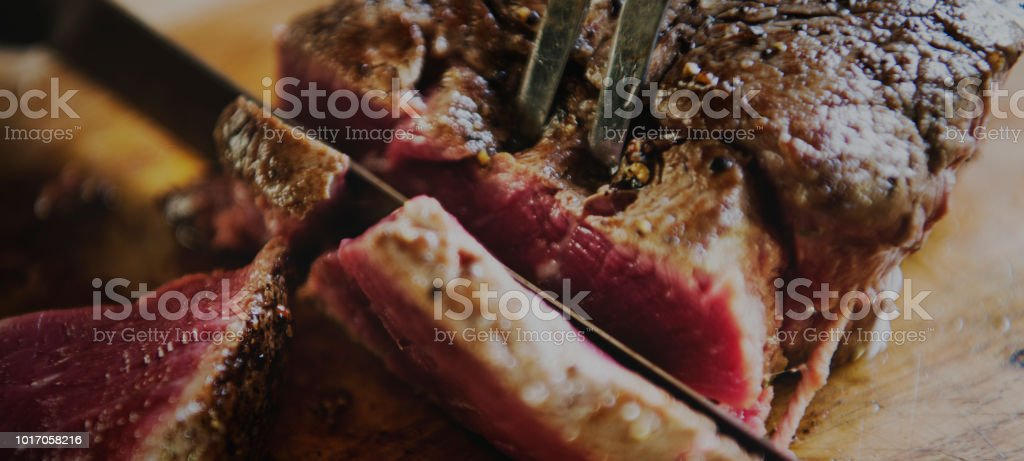 Cutting a cooked fillet steak food photography recipe idea stock photo
