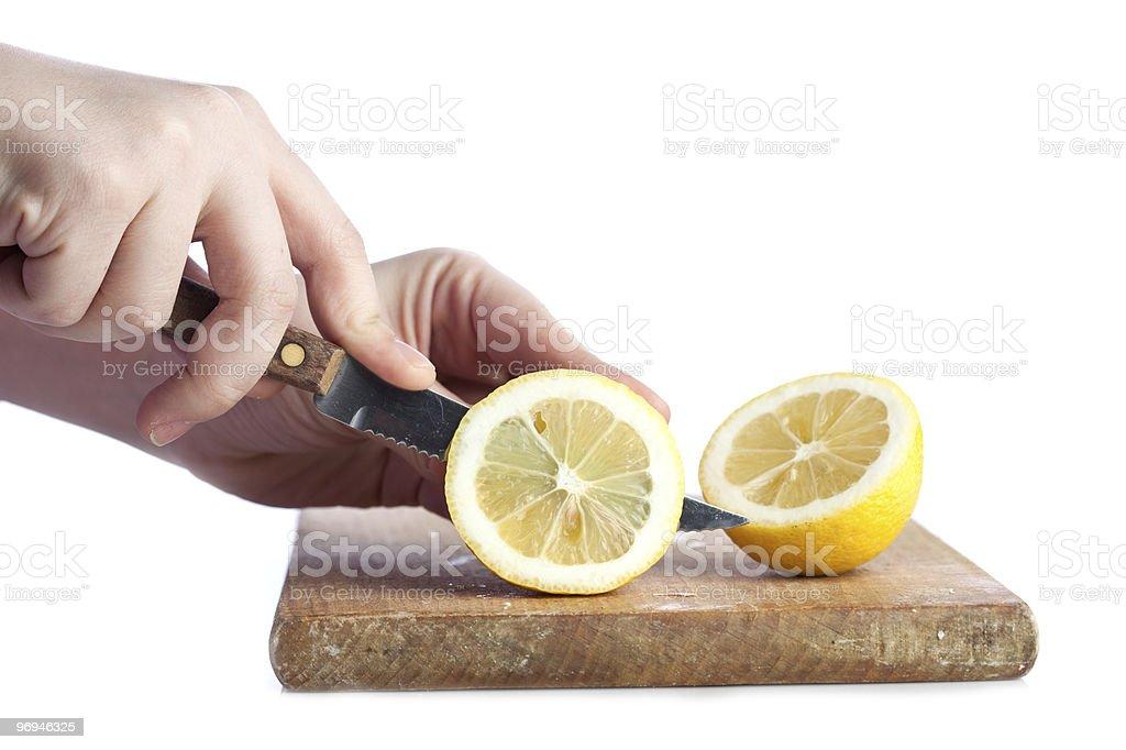 Cutting a lemon isolated on white background royalty-free stock photo