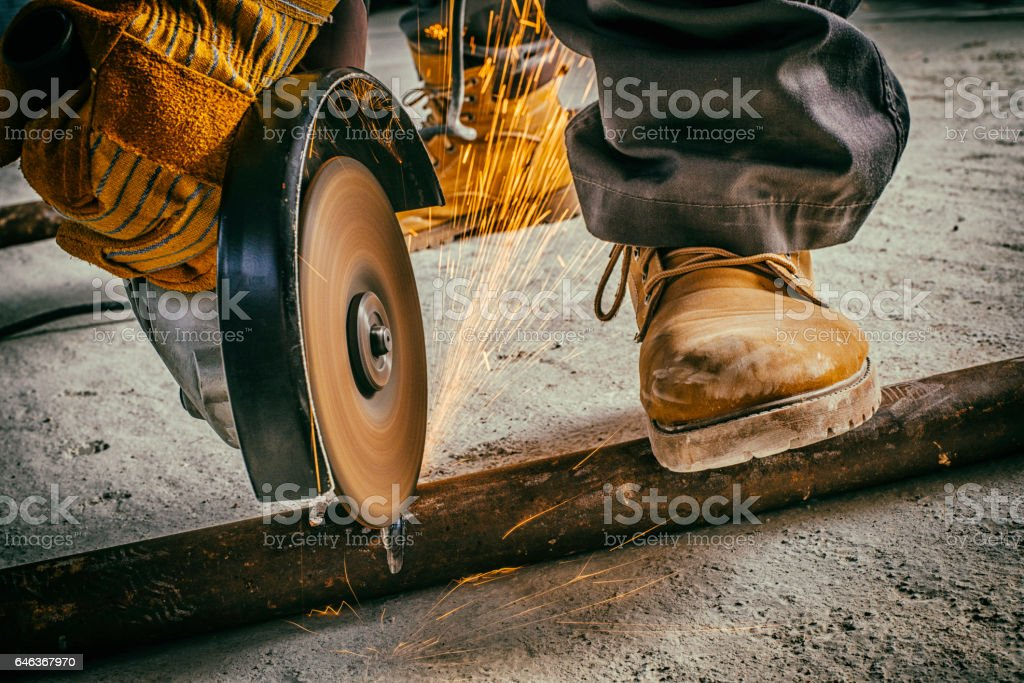 Cutting a metal rod with a circular saw stock photo