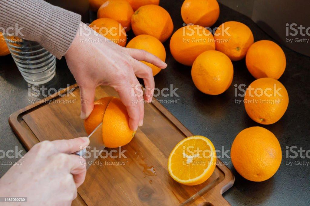 Het snijden van een sinaasappel om verse en gezonde jus d'orange te maken. Gezond lifestyle concept. foto