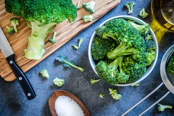 Cutting and cooking broccoli on grey textured backdrop Top view of a bowl full of broccoli branches surrounded by a wooden cutting board with a entire broccoli and a kitchen knife on top, an olive oil bottle, a metal colander and a little wooden tray with salt on a grey textured backdrop. Low key DSLR photo taken with Canon EOS 6D Mark II and Canon EF 24-105 mm f/4L broccoli stock pictures, royalty-free photos & images