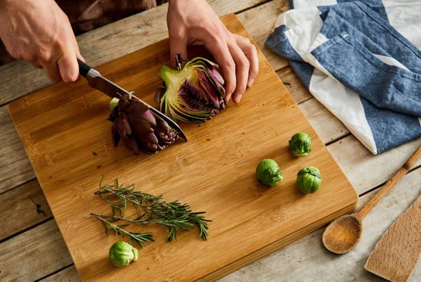 Cutting artichoke on a cutting board stock photo
