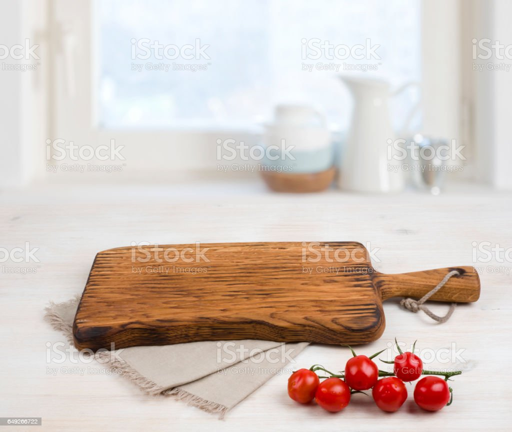Cutting board above linen tablecloth on wooden table. Cooking concept stock photo