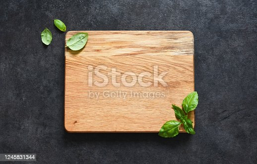 istock Cutting board and basil on a black stone background. Food background with place for text. View from above 1245831344