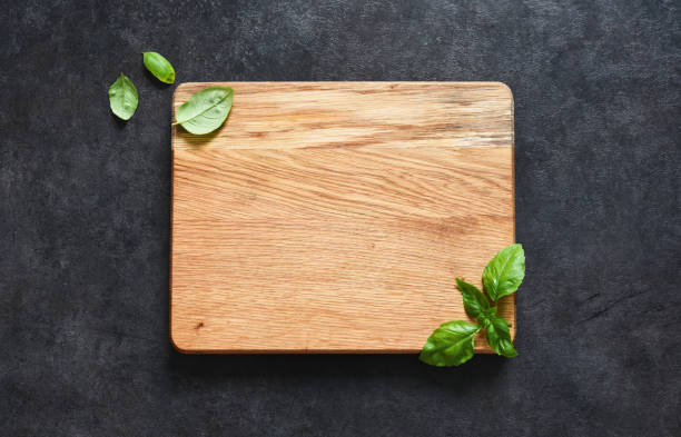 Cutting board and basil on a black stone background. Food background with place for text. View from above Cutting board and basil on a black stone background. Food background with place for text. View from above plank timber stock pictures, royalty-free photos & images