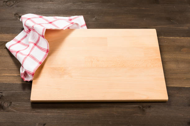 Cutting board and checkered tablecloth isolated on wooden background stock photo