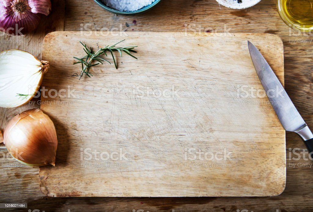 Cutting board and vegetables on a wooden table stock photo