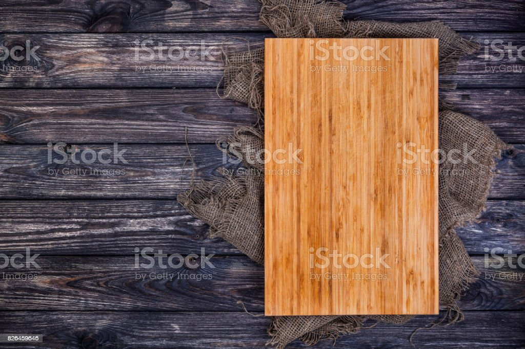 Cutting board on dark wood background, top view stock photo