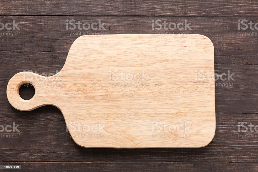 Cutting board on the wooden background. Top view stock photo