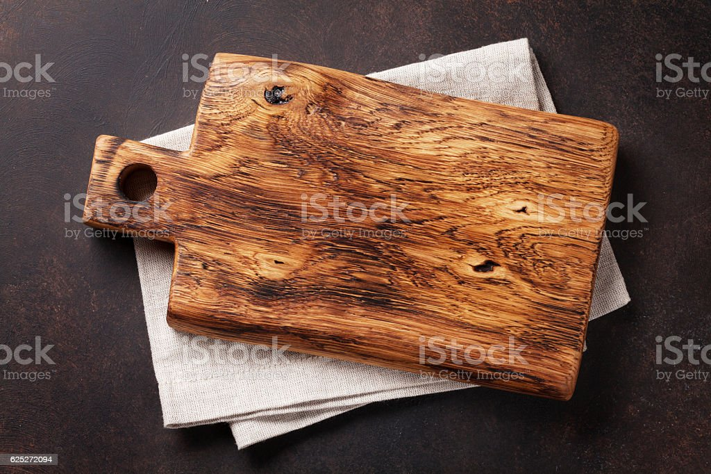 Cutting board over towel on stone kitchen table stock photo