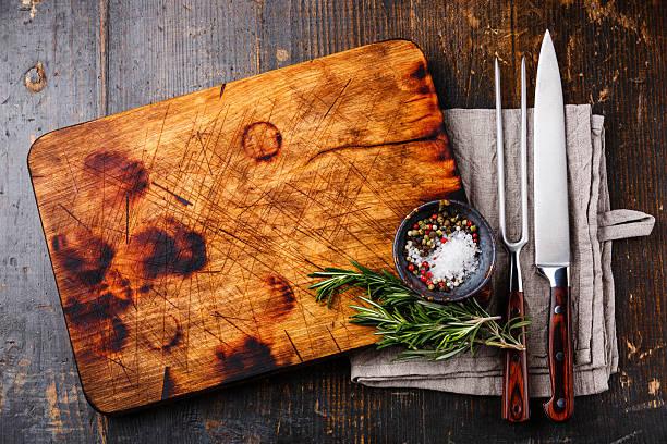 schneidebrett, paprika und rosmarin mit gabel und messer - tranchieren stock-fotos und bilder