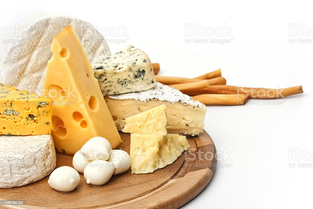 Cutting board with assorted cheeses stock photo
