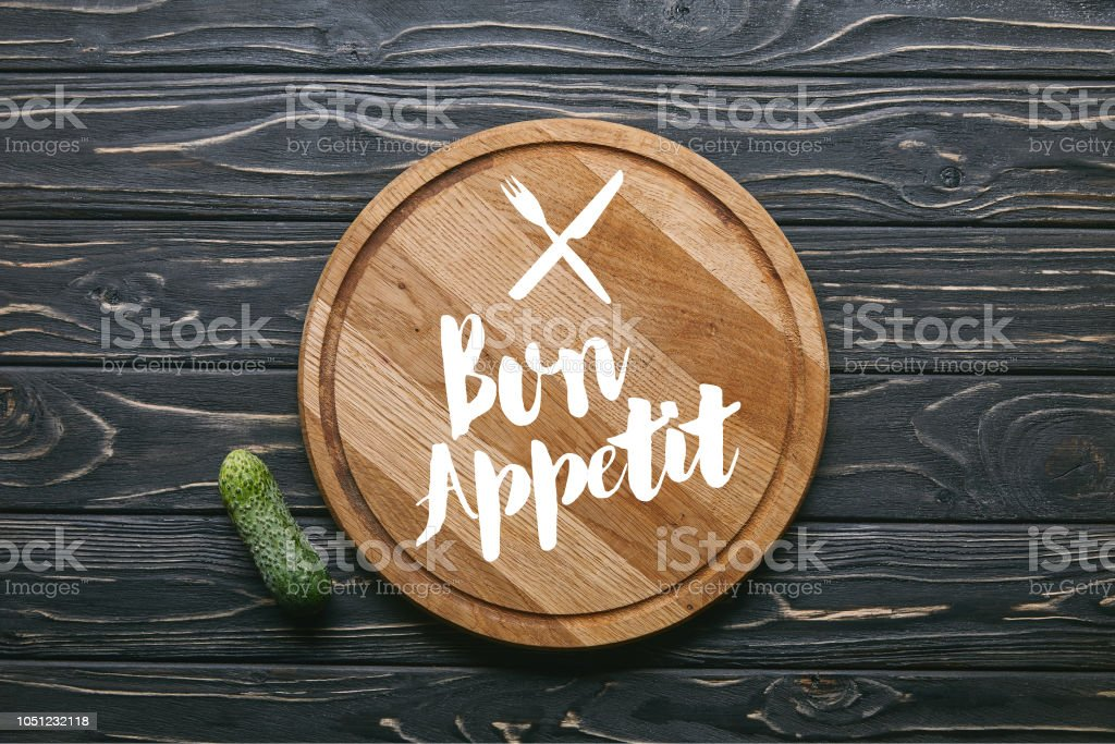 Cutting board with 'bon appetit' lettering and cucumber on dark wooden table stock photo
