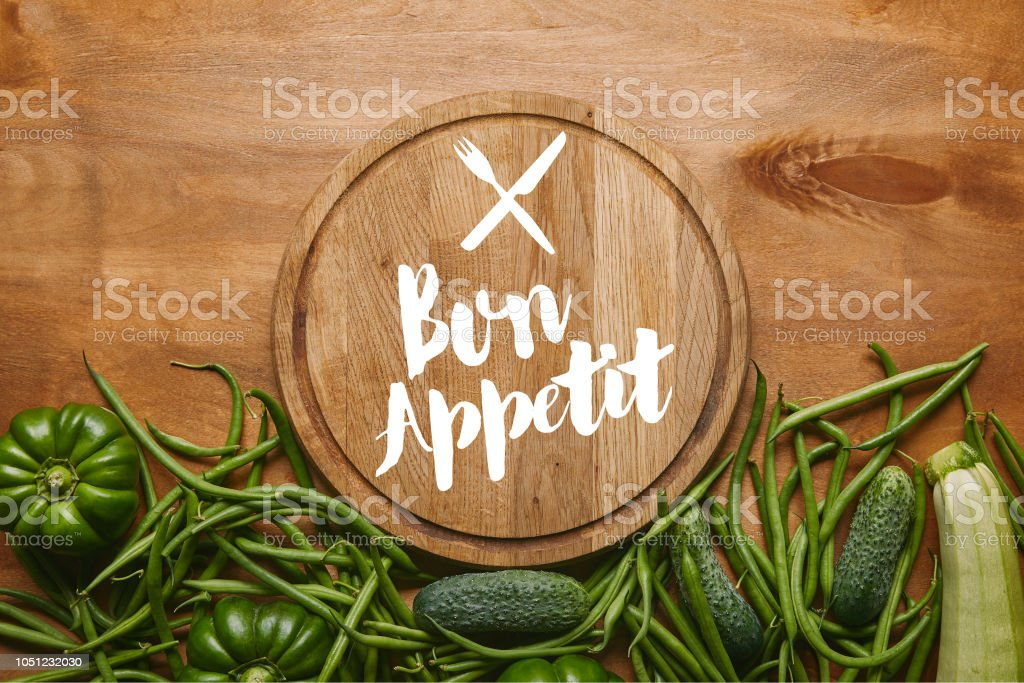 Cutting board with 'bon appetit' lettering with green vegetables on wooden table stock photo