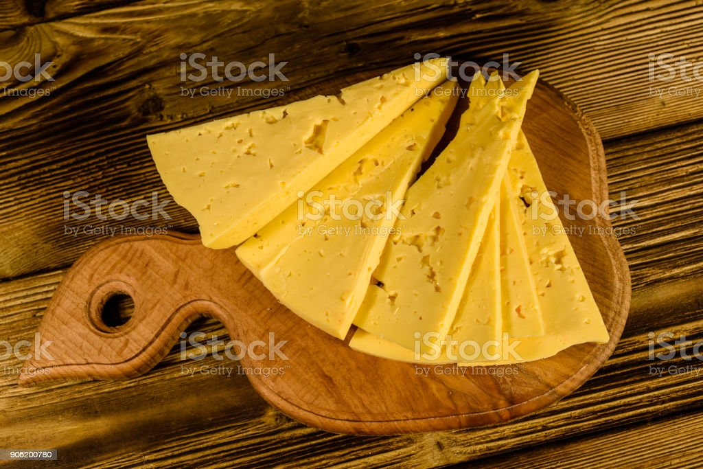 Cutting board with chopped cheese on rustic wooden table. Top view
