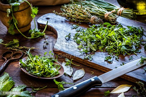Cutting board with chopped parsley and a kitchen knife on top surrounded by a wooden tray with more chopped parsley, some dried bay leaves and at the background are a few aromatic herbs like thyme, chive, and rosemary tied in bunches. At the left top corner is a mortar with coriander and a vintage scissor. Low key DSLR photo taken with Canon EOS 6D Mark II and Canon EF 24-105 mm f/4L