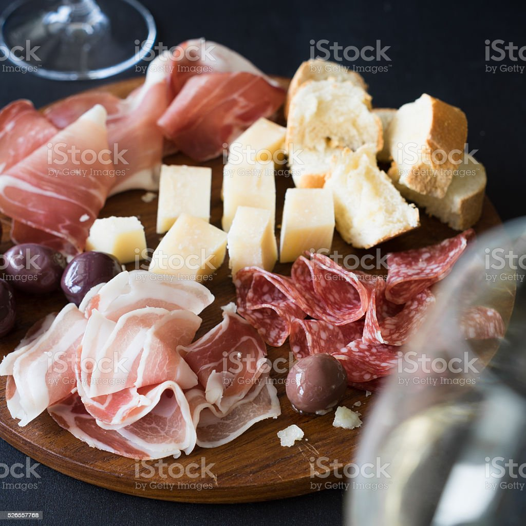 Cutting board with cured meat, cheese and olives stock photo