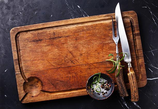 schneidebrett mit gabel und messer tranchierbesteck - tranchieren stock-fotos und bilder