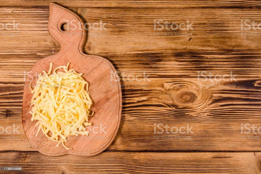 Cutting board with grated cheese on rustic wooden table. Top view