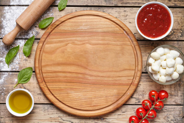 Cutting board with pizza ingridients: mozzarella, tomatoes sauce, basil, olive oil, cheese, spices. Italian pizza preparation wooden table. Traditional food. stock photo
