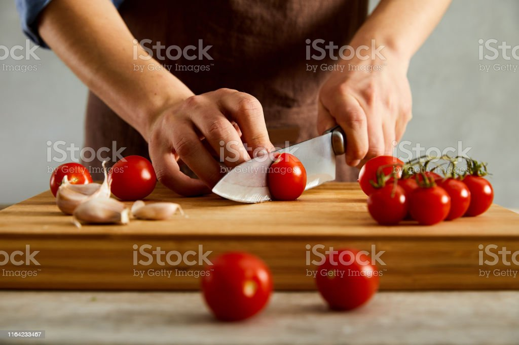 Close up of male hands cutting cherry tomatoes on a cutting board.
