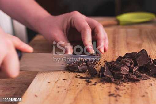 cutting dark chocolate with a knife in the kitchen on a wooden table