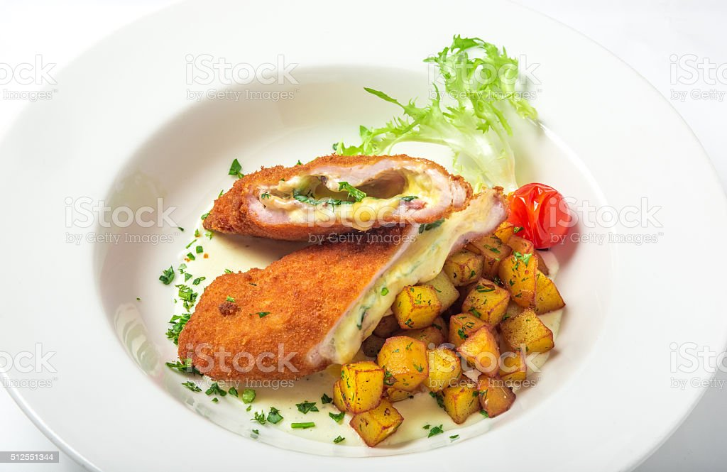 Cutting cordon bleu with cheese, turkey, crackers crumbs, potatoes. stock photo
