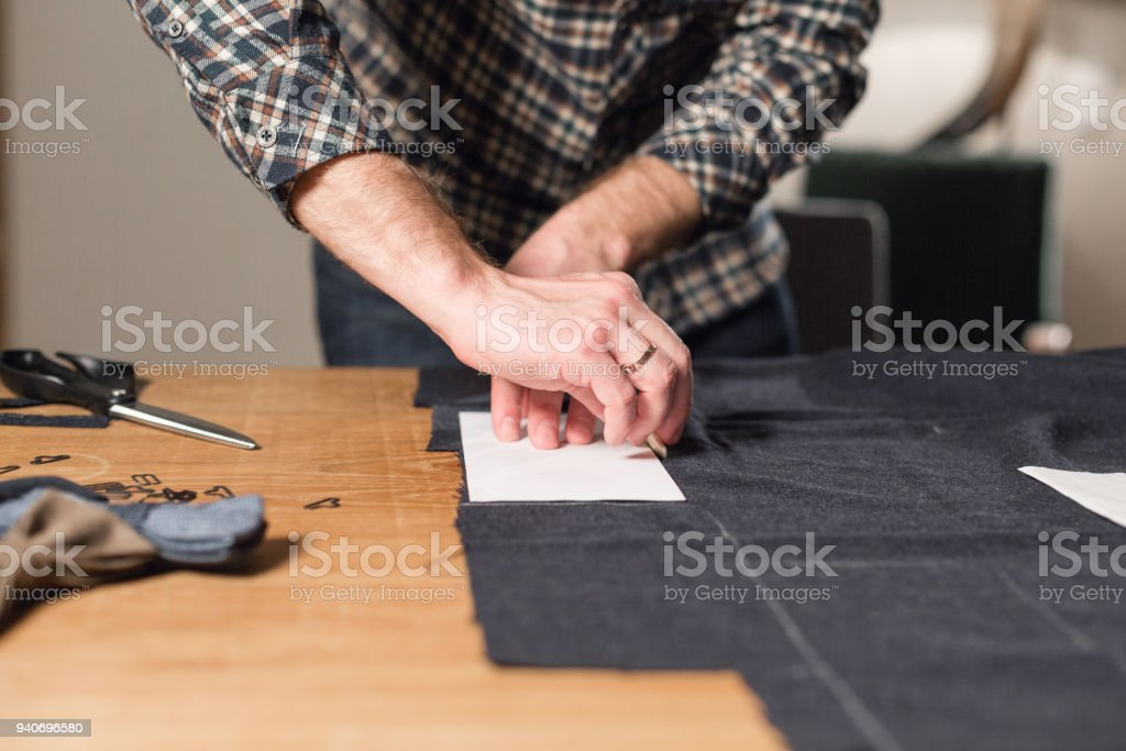 Cutting dark wool fabric. the line pattern. Young man working as a tailor and using a sewing machine in workshop. stock photo