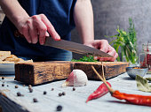 Human hands chopping dill on wooden cutting board. Close-up