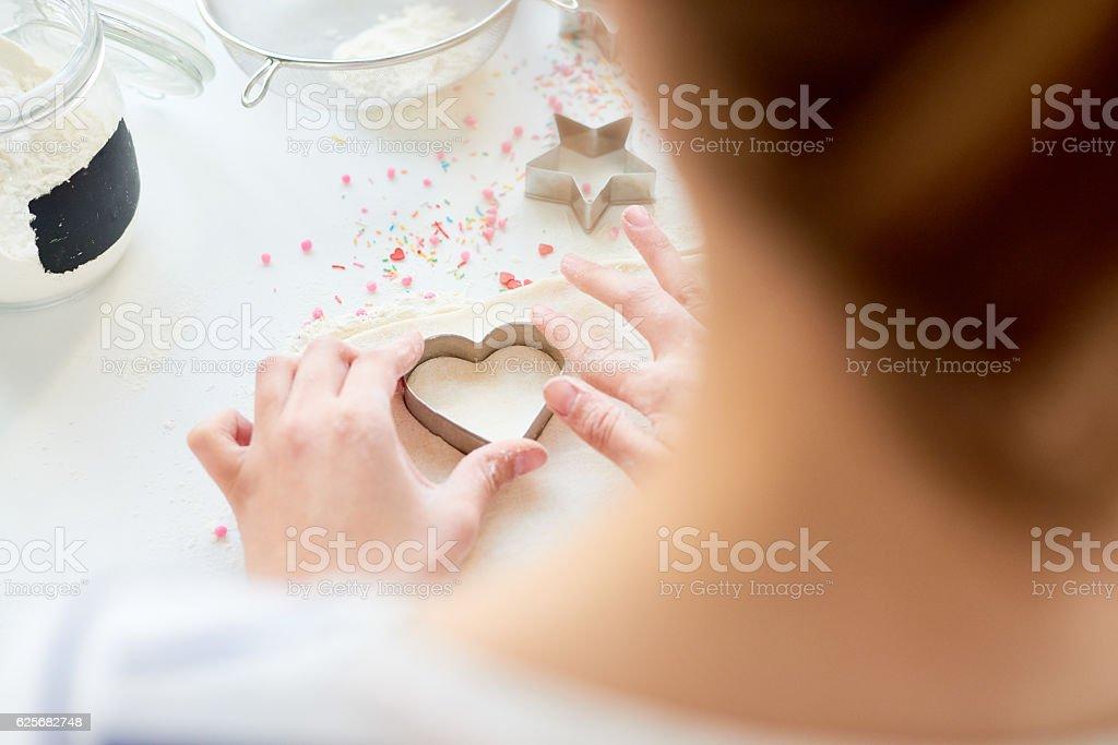 Cutting dough in shape of heart stock photo