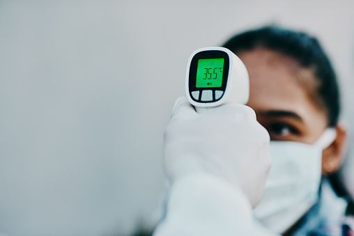 Shot of a young woman getting her temperature taken with an infrared thermometer by a healthcare worker during an outbreak