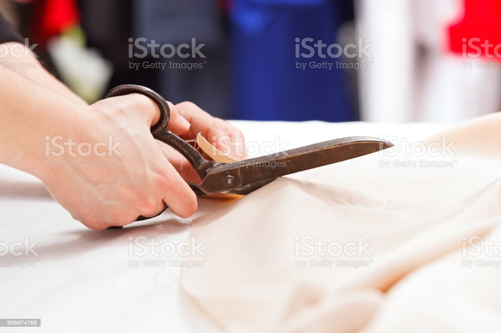 Cutting fabric with big old steel scissors stock photo